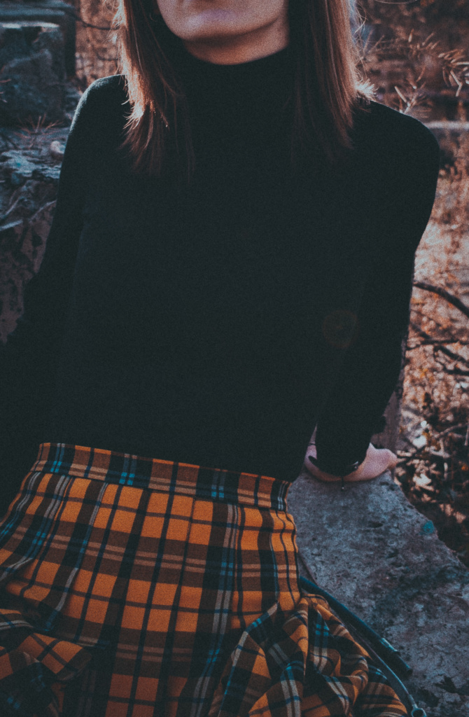 woman in yellow plaid skirt and black turtleneck