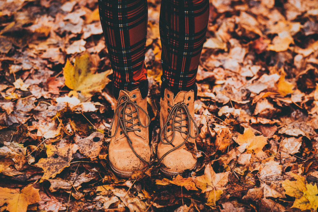 Woman in plaid tights in fall leaves
