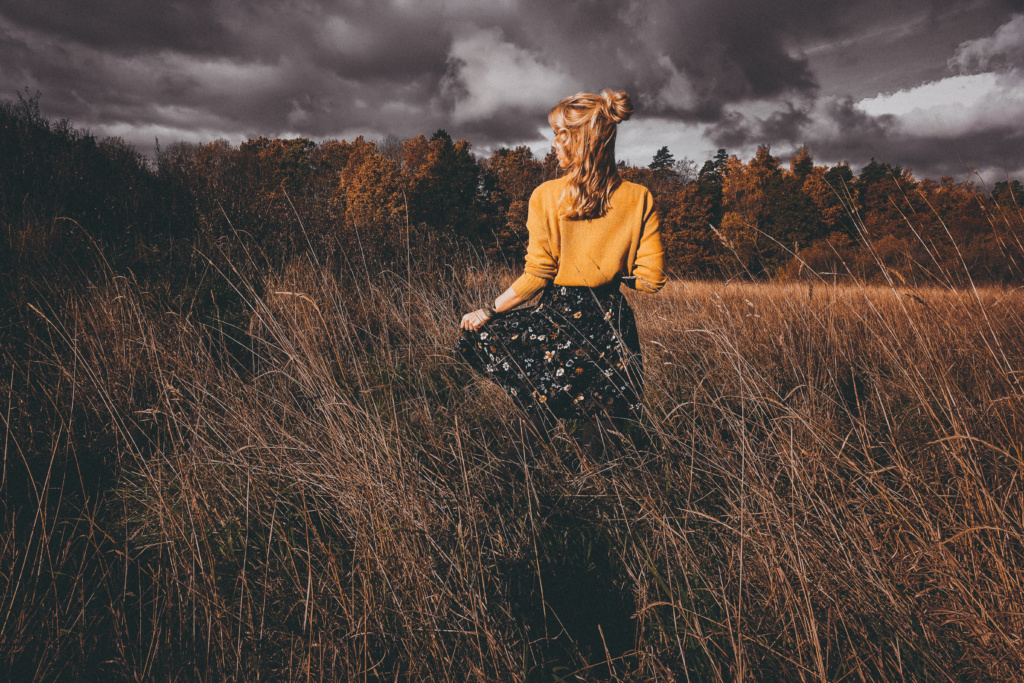 Girl in yellow sweater in field near the woods