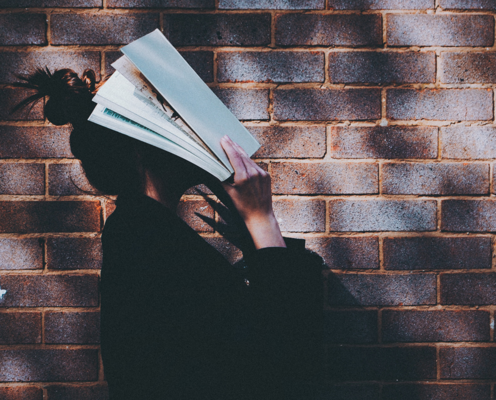 Girl with book in front of brick wall