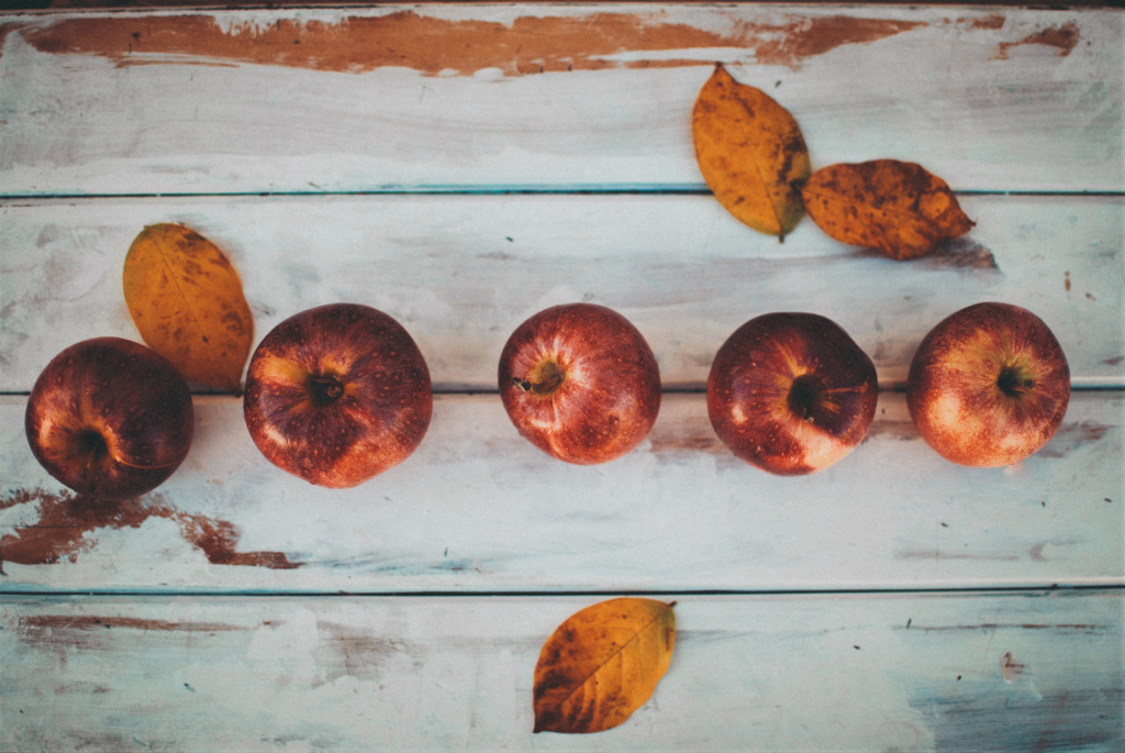 Red apples and yellow fall leaves on white wooden background