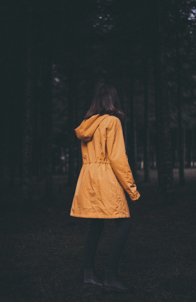 Woman in yellow coat in the woods